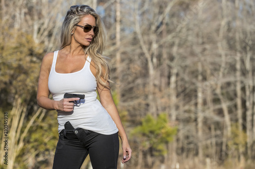 Photo  Gorgeous Blonde Model Protecting Herself With A Pistol