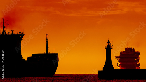 Fotografía  FREIGHTER AND CRUISER SHIP - Ships on water route at sunrise on the roadstead of