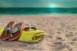 Handtuch, Flip Flops und Sonnenbrille am Strand. Sonnenuntergang am Abend.