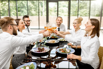 Fototapeta Group of business people dressed in white shirts clinking with wine glasses during a business lunch with delicious meals at the modern restaurant