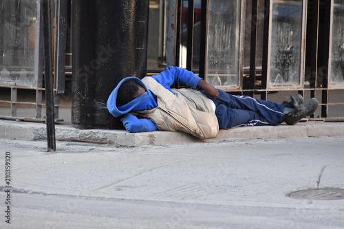 Fototapeta A homeless man sleeps on a street in downtown Montreal-Canada
