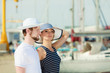 Tourist couple in marina against yachts in port