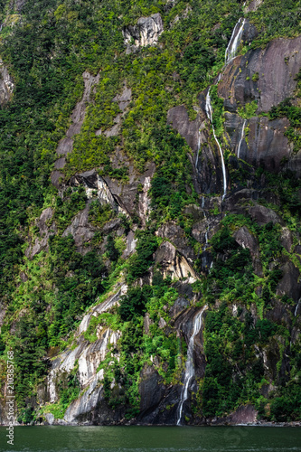 Foto op Plexiglas Natuur A stunning scene of nature with many waterfalls from the high mountain at Milford Sound, New Zealand.