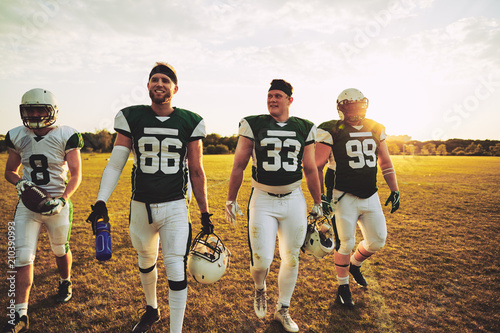 Fototapeta Smiling team of American football players walking off a field