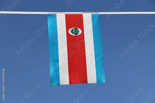 Fotografía  Mini fabric rail flag of Costa Rica in Tricolor red blue and white with National coat of Arms, hanging on the rope cloth on blue sky background