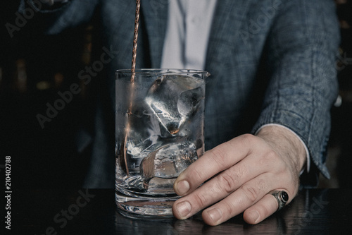 An underexposed image of barman's hands stirring ice in a mixing