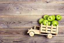 Toy Wooden Truck With Green Apples In The Back On Wooden  Background.