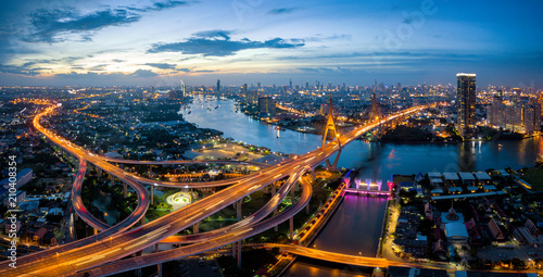 Obraz na płótnie Aerial view of Bhumibol suspension bridge cross over Chao Phraya River in Bangkok city with car on the bridge at sunset sky and clouds in Bangkok Thailand