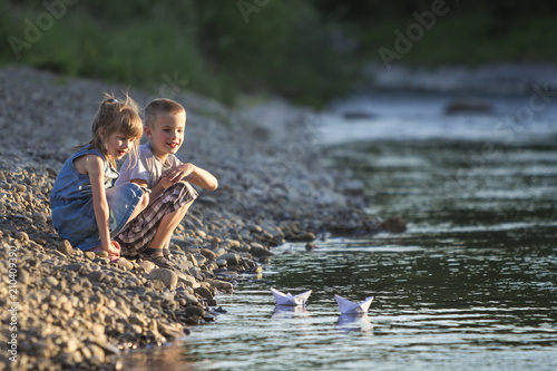 Two smiling blond children, boy and girl playing with white paper boats on river bank on bright summer blurred blue background Fototapeta