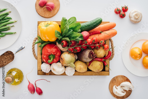 Fototapeta top view of box with fresh raw vegetables and plates isolated on white obraz