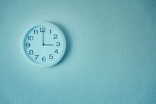 Round White Clock On A Blue Wall. The Clock Shows Three O'clock In The Afternoon.