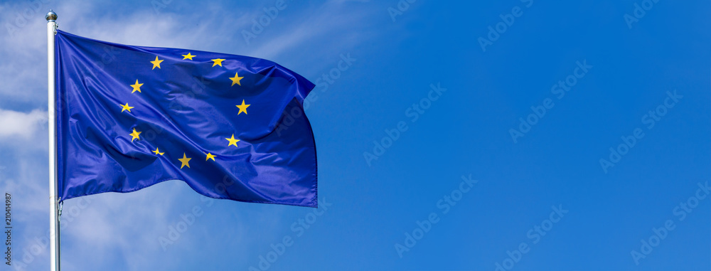Fototapeta Flag of the European Union waving in the wind on flagpole against the sky with clouds on sunny day, banner, close-up