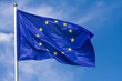 canvas print picture - Flag of the European Union waving in the wind on flagpole against the sky with clouds on sunny day, close-up
