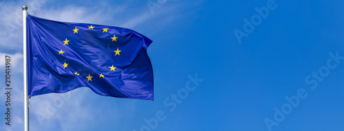 Foto  Flag of the European Union waving in the wind on flagpole against the sky with c