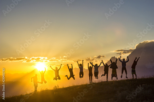 Foto op Canvas Paarden group of people with hands up jumping on grass in sunset mountains
