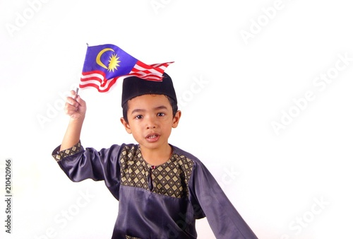 Young Malay Asian boy wearing Malay traditional clothe baju melayu with skull cap or songkok holding and waving Malaysia flag isolated on white