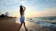 A girl in a white dress enters the sea at sunset. I am happy with the sea and the beach. Experiencing freedom. Goes into the water,