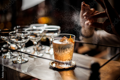 Photo sur Aluminium Cocktail Bartender decorating fresh old fashioned summer cocktail with ice and orange peel