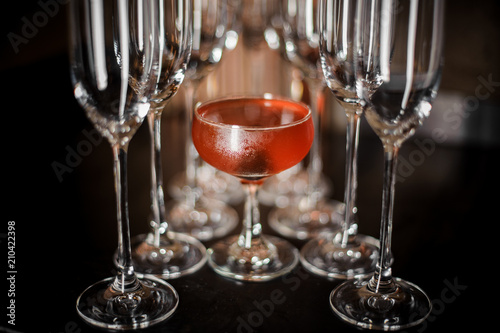 Spoed Foto op Canvas Alcohol Elegant cocktail glass filled with tasty red alcoholic cocktail among empty champagne glasses
