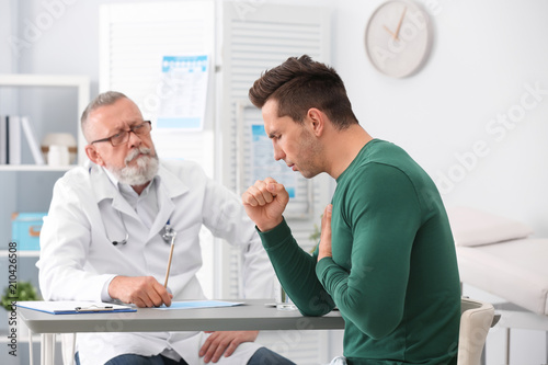 Fotografiet  Coughing young man visiting doctor at clinic