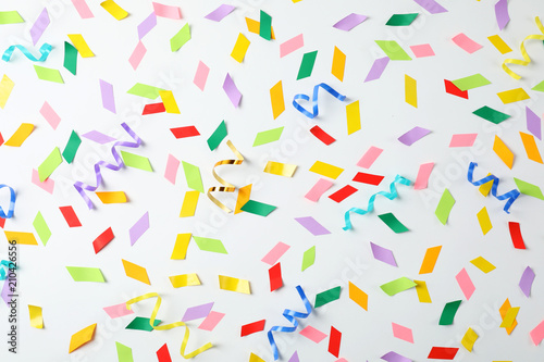 Fotografia  Colorful confetti and streamers on white background, top view
