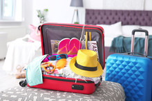 Open Suitcase With Different Clothes And Accessories For Summer Journey On Ottoman Chair
