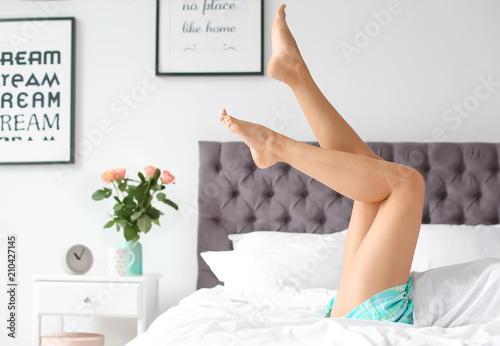Fototapeta Young woman with sexy legs resting on bed at home