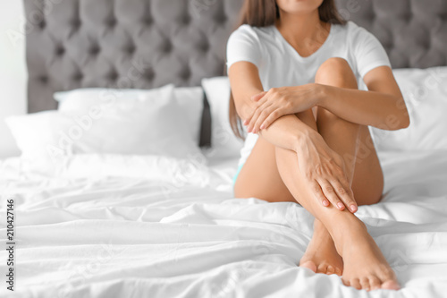 Fotografía Young woman with sexy legs resting on bed at home