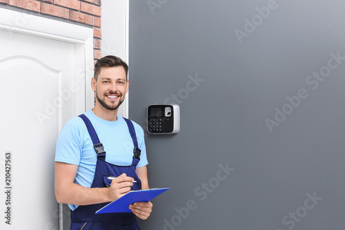 Fotomural Male technician with clipboard near installed alarm system indoors