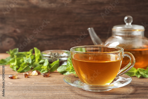 Foto op Plexiglas Thee Cup with hot aromatic mint tea on wooden table