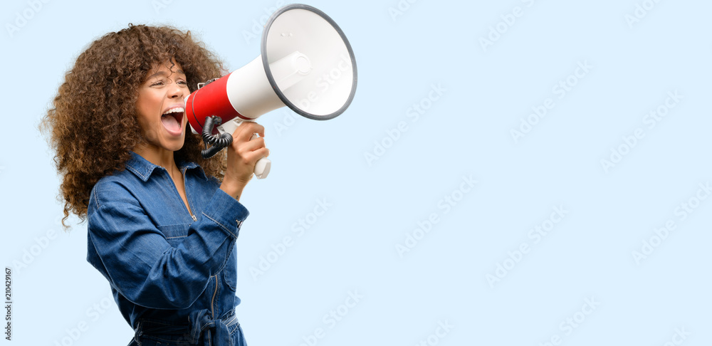 Fototapeta African american woman wearing blue jumpsuit communicates shouting loud holding a megaphone, expressing success and positive concept, idea for marketing or sales
