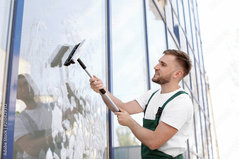 Fototapeta Male cleaner wiping window glass with squeegee from outside