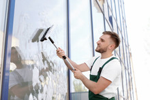 Male Cleaner Wiping Window Gla...