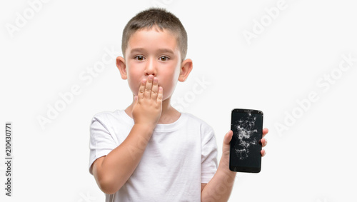 Fototapeta Dark haired little child holding broken smartphone cover mouth with hand shocked with shame for mistake, expression of fear, scared in silence, secret concept obraz