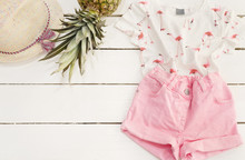 Pink Denim Shorts And Shirt, Straw Hat, Pineapple. White Old Wooden Background