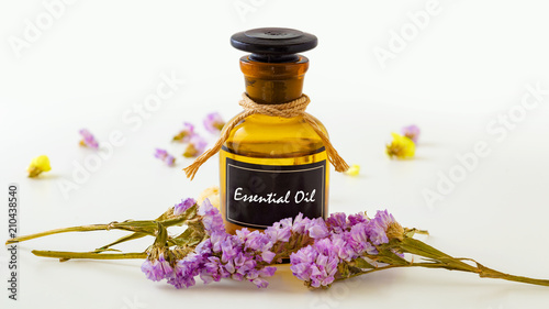 Essential oil with flowers on white