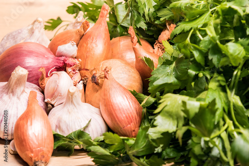garlic onion shallot parsley on a wooden board