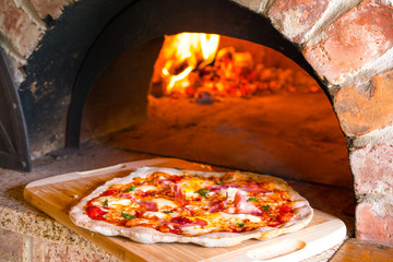 Rustic home-made pizza prosciutto baked in a wood fired brick oven with fire ...