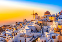 Sunset In Oia Town, Santorini Island, Greece. Traditional And Famous White Houses And Churches  With Blue Domes Over The Caldera, Aegean Sea.