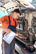 The mechanic pours engine oil into the engine of the truck