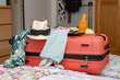 Kleidungsstücke für den Sommerurlaub auf einem geschlossenen roten Koffer vor großem Kleiderschrank im Schlafzimmer