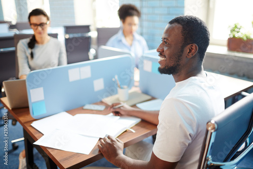 Fotografía  Happy young businessman in casualwear sitting by individual workplace and organi