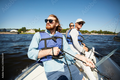 Photo Stands Water Motor sports Group of men in protective lifejackets and sunglasses floating on yacht or motor boat on summer day