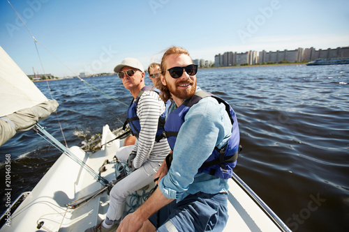 Active men in sunglasses sitting on yacht while floating in lake on hot summer day
