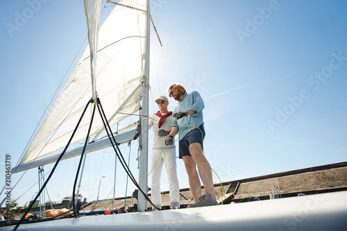 Two active men preparing sail of yacht while going to have