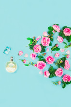 Flatlay Of Spraying Pink Tea Rose Flowers And Petals From Beautiful Perfume Bottle On The Blue Background. Fresh Concept With Luxury Aroma. Beauty Cosmetic. Vertical. Selective Focus. Copy Space.