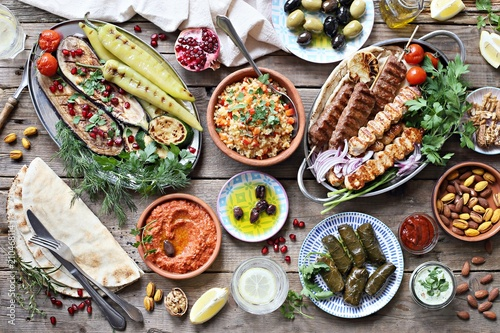 Middle eastern, arabic or mediterranean dinner table with grilled lamb kebab, chicken skewers with roasted vegetables and appetizers variety serving on wooden outdoor table. Overhead view.