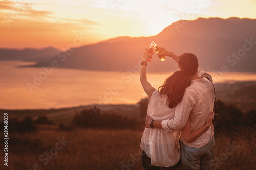 Foto Young couple having good times in nature looking at the sunset on Boka Bay