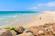 Unidentified man standing on sandy Tarifa beach and looking at ocean, Costa de la Luz, Spain
