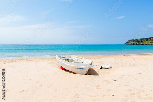 Fotografia White fishing boat on white sand Bolonia beach and blue sea view, Andalusia, Spa